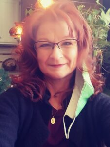 woman with red hair and glasses smiling into the camera.